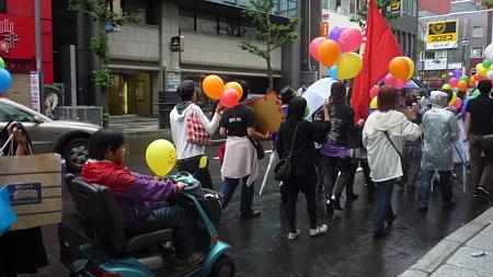 駅前通に突き当たる。電動車椅子で参加する人もいる。