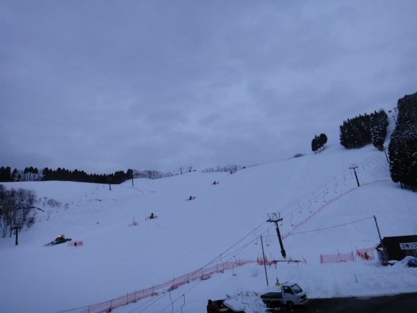 暗くなりかけたゲレンデを圧雪車が走る